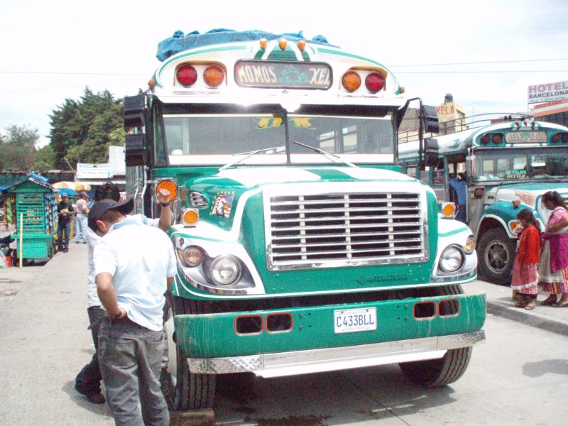 A man in a black hat standing in front of a green and white chicken bus in Quetzaltenango, Guatemala.