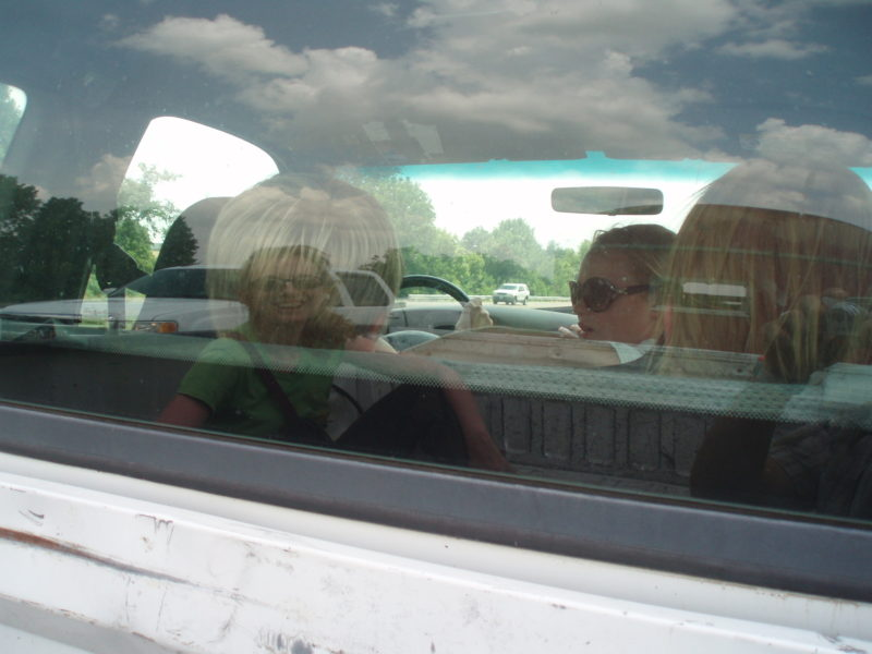A reflection of a smiling woman in the glass of a windshield.